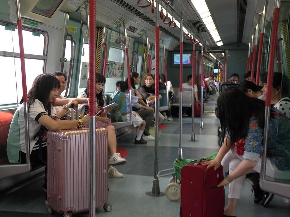 另外,香港地铁的装修也充满了当地的特色,每个站用不同颜色的马赛克作墙壁贴面,如湾仔站的绿色、铜锣湾站的紫色、中环站的红色、金钟站的橘黄色。图为2017年5月18日,人们乘坐地铁出行。他们中也有是从事职业或者业余的代购活动。(图源:VCG)