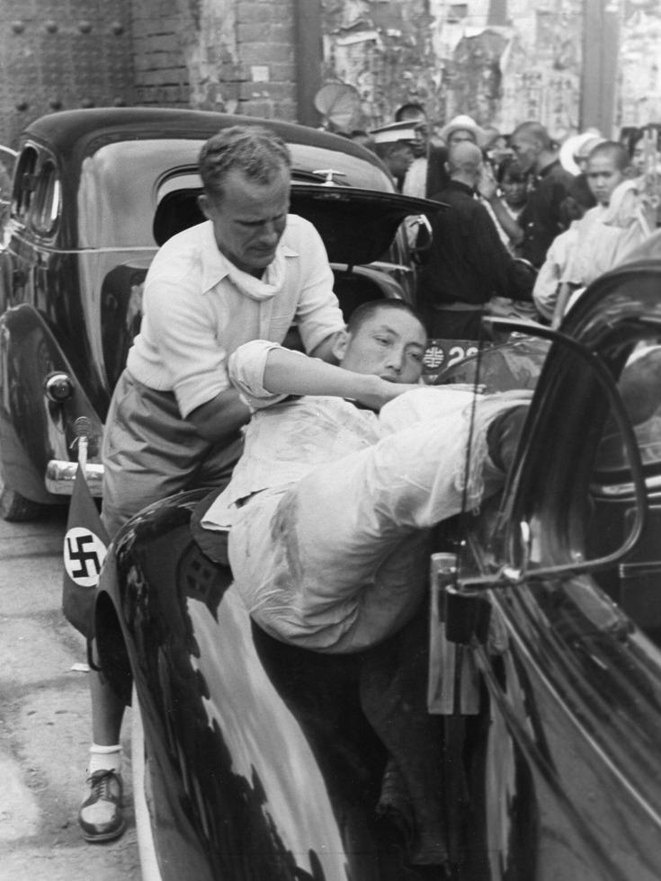 受伤的29军士兵正在被人从 Walter Bosshard 的车上抬下来。(图源:VCG)